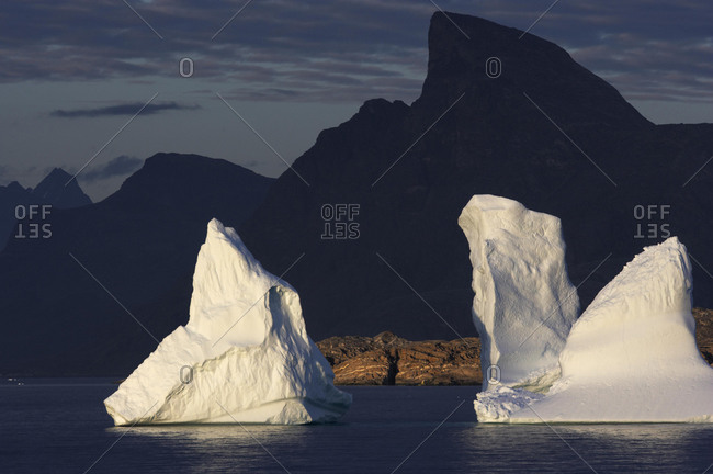 Icebergs in the evening light, in front of the mountain silhouette in Prins Christian Sund, South Greenland, Greenland, North America