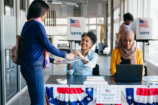 Volunteer helping citizen at polling place