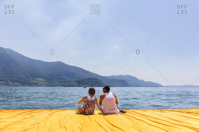 Lake Iseo, Lombardy, Italy - June 22, 2016: Couple sitting on The Floating Piers, by Christo and Jeanne-Claude.