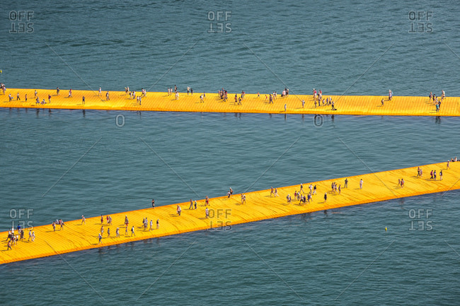 Lake Iseo, Lombardy, Italy - June 22, 2016: People walking on The Floating Piers, by Christo and Jeanne-Claude.