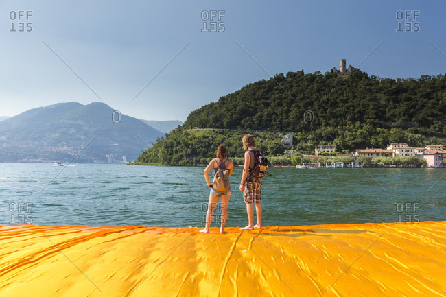 Lake Iseo, Lombardy, Italy - June 22, 2016: Young people experiencing The Floating Piers, by Christo and Jeanne-Claude.