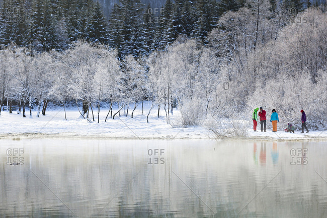 Tarvisio, Julian Alps, Italy - October 10, 2016: Hikers at Fusine Lake in the winter