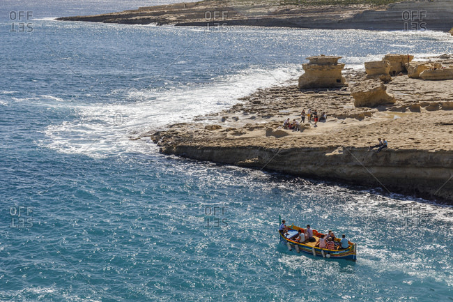 Malta - October 29, 2017: Luzzu boat carrying travelers in the sea of St. Peter's Pool