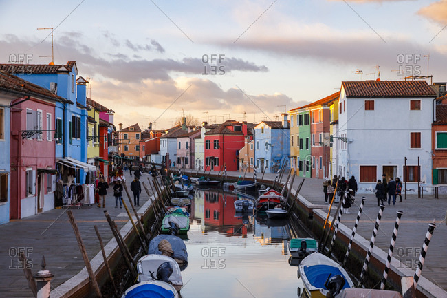 Venice, Italy - January 2, 2019: Colorful houses in Burano with canal and moored boats