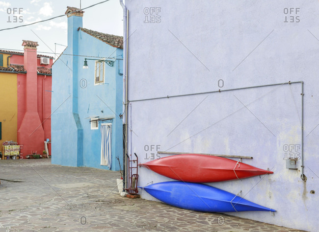 Canoes hanging on the wall of the colorful Burano village, Venice, Italy
