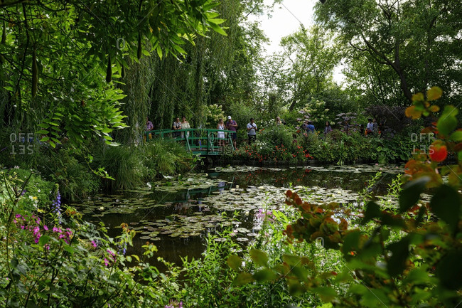 People standing a wooden bridge of the water lily pond in Manet's Garden