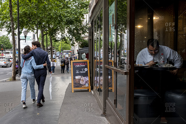 Paris, France - June 8, 2019: Couple kissing on the street while man alone is entertained with his mobile phone in a coffee shop