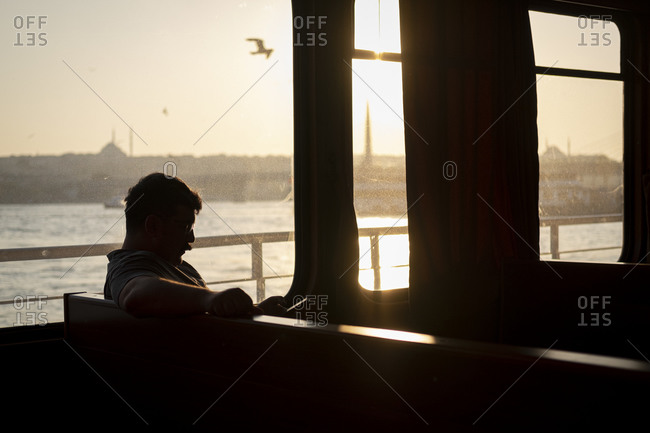 Istanbul, Turkey - August 25, 2019 : Man checking his mobile phone on a trip in an Istanbul ferry