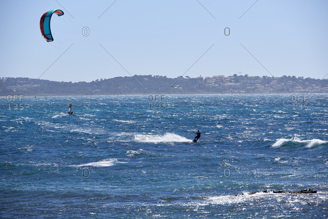 Hyeres, Var, France - April 5, 2018: Kite surfers and windsurfers on famous beach l'Almanarre
