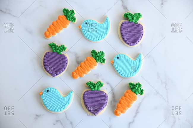 Overhead view of colorful bird, carrot and turnip Easter cookies on marble surface