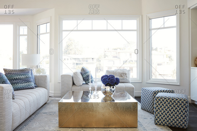 Laguna Beach, California - May 17, 2015: Living room interior with gold coffee table and large windows