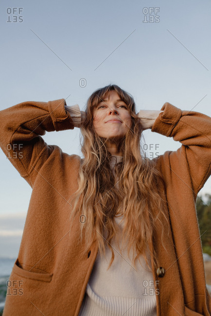 Portrait of a woman with long wavy hair looking up to the sky