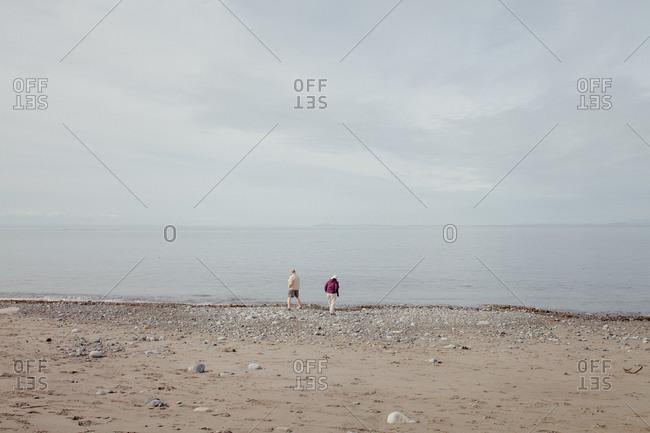 Tourists walking on rocky beach on the coast of Washington State, USA
