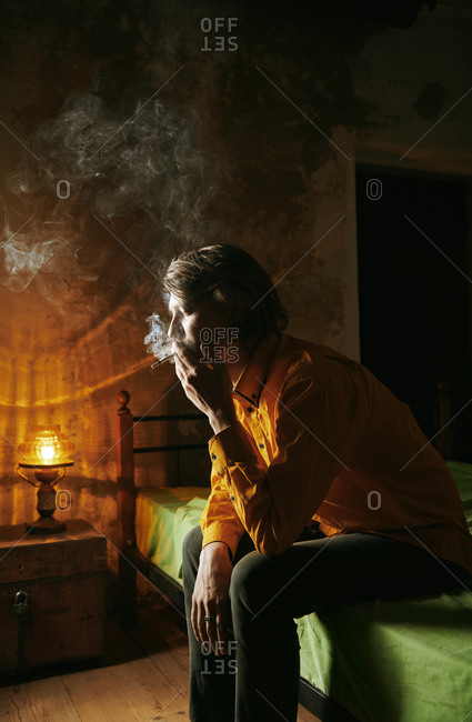 Man smoking cigaratte and sitting on the bed