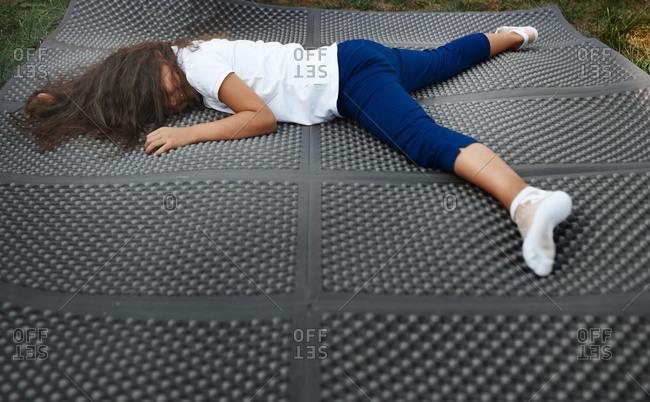 Cute girl resting on a rubber mat in backyard