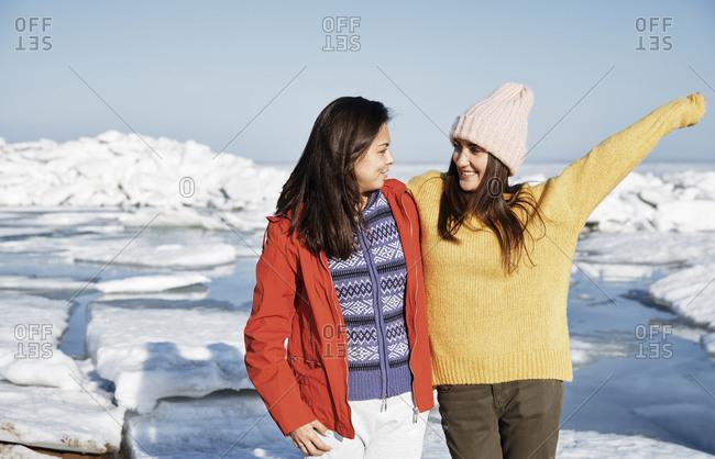 Two happy girlfriends outdoors enjoying winter landscape