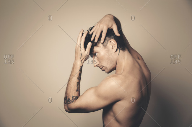 Profile portrait of an athletic half-naked man raising his arms around his head in studio