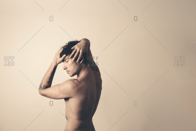 Profile portrait of an athletic half-naked man raising his arms around his head in studio with his eyes closed