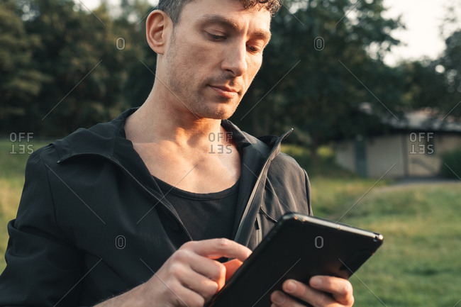 Close-up portrait of a young adult using his tablet outdoors