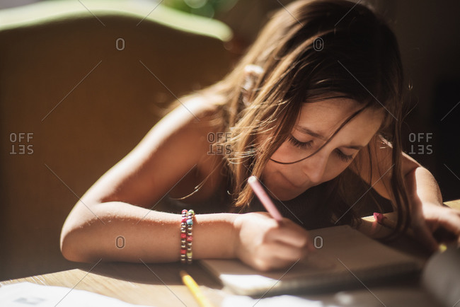 Girl concentrating while trying to draw a picture on a sketch pad