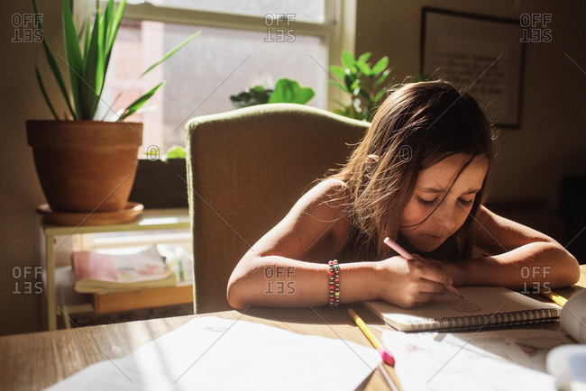 Girl concentrating while drawing a picture on a sketch pad