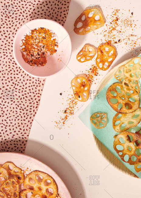 Lotus root chips served with paprika salt on a pink patterned paper background