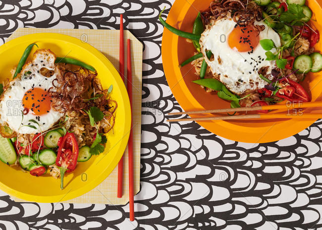 Nasi Goreng with fried egg, fresh chilis and cucumber slices on bright yellow and orange plates