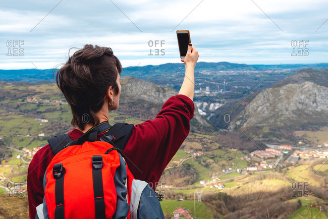 Back view of unrecognizable woman with backpack standing with arm raised and taking shot with smartphone of wonderful scenery with small villages and town in valley against foggy ridges at horizon under cloudy sky in Asturias