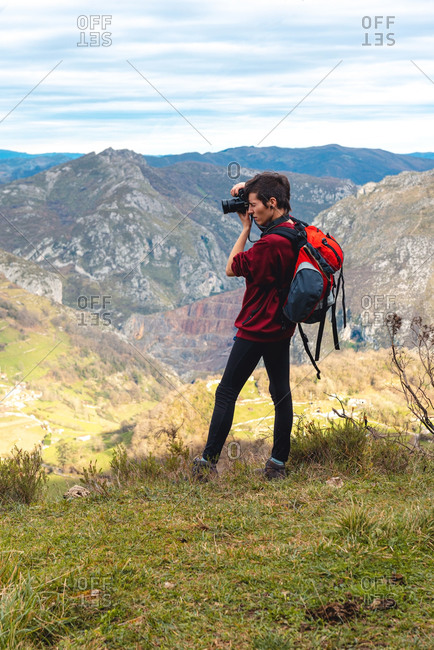 Side view of woman with backpack standing on glade and taking shot with camera of magnificent valley against foggy ridges at horizon under sky with fluffy clouds in Spain