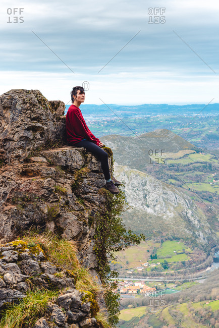 Side view of tourist sitting on edge of cliff enjoying freedom and admiring amazing scenery of countryside located in valley at mountain foothill against foggy forested hills and plain under sky with lush gray clouds in Spain