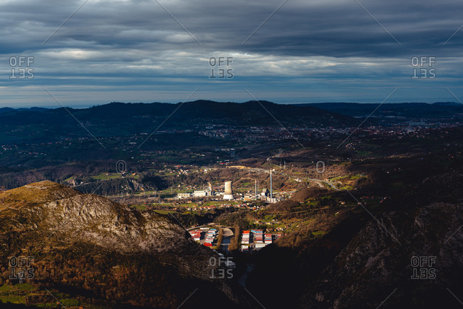 From above factory in valley against city at foothill of mountains at horizon under gray cloudy sky in Monsacro