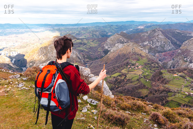 Back view of unrecognizable hiker with backpack and stick standing with arms outstretched and enjoying freedom viewing majestic scenery of countryside located along river shore in valley against foggy ridges at horizon under cloudy sky in Spain