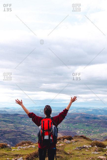 Back view of unrecognizable hiker with backpack standing with arms outstretched and enjoying freedom viewing majestic scenery of countryside located along river shore in valley against foggy ridges at horizon under cloudy sky in Spain
