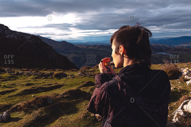 Back view of provocative confident female traveler with trendy hairstyle in casual clothes lighting cigarette while looking away and enjoying wonderful scenery of highland under dramatic clouds in evening in Spain
