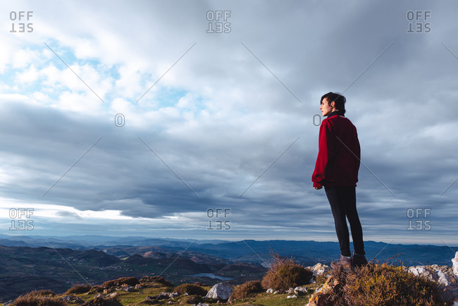 hiker standing and enjoying freedom viewing majestic scenery of countryside located along river shore in valley against foggy ridges at horizon under cloudy sky in Spain