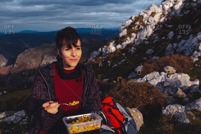 woman in warm jacket holding plastic container of chickpea with veggies having lunch on meadow while hiking in Spain