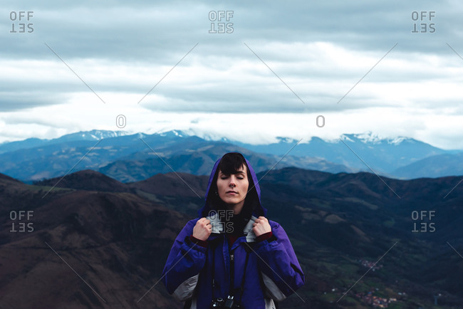 woman tourist in violet jacket with backpack with close eyes in picturesque mountain ridges under cloudy sky while standing in Monsacro