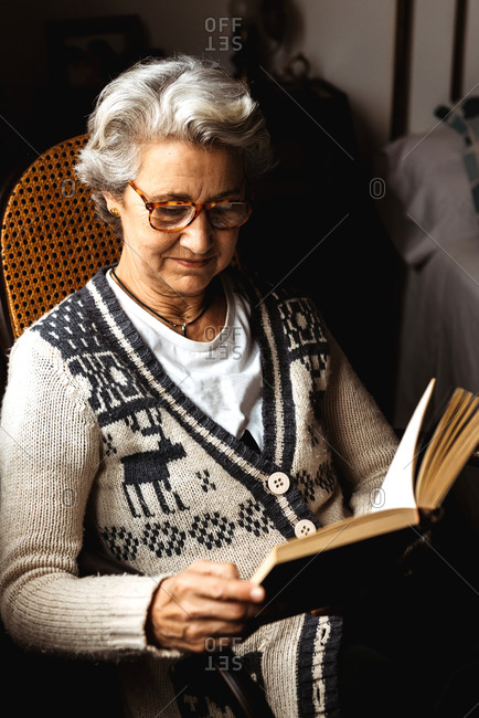 Elderly woman reading by window with enthusiasm