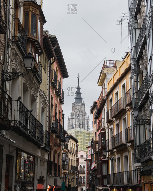 From below of narrow street of city Toledo in Spain with old residential buildings and cathedral in background against gray cloudy sky