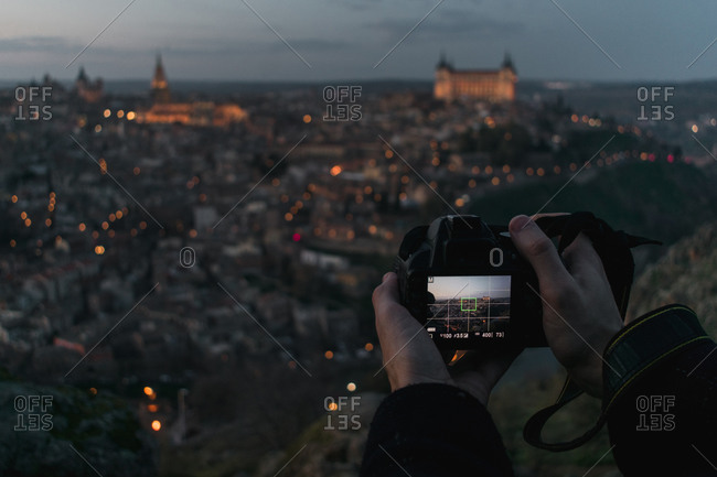 Crop hands of male photographer with camera standing on hill and taking photo of old Spanish city Toledo with castles in twilight