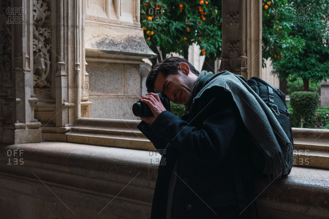 Side view of male traveler with backpack standing next to window and taking picture with camera while visiting old historic stone building in Spanish city Toledo
