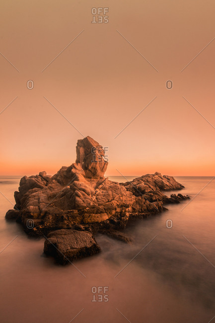 Amazing view of big rough cliff among calm sea in warm light of evening sky