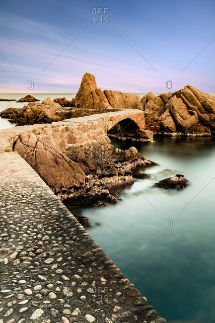 From above of empty rocky bridge and rough cliffs among blue clear ocean with colorful heaven on background