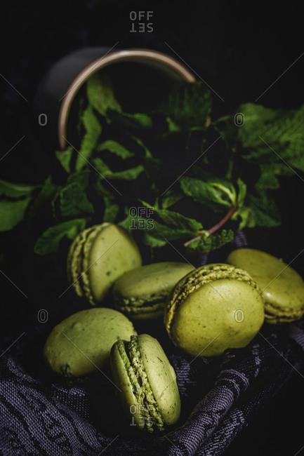 Homemade green macarons green with mint on dark background. Dark food.