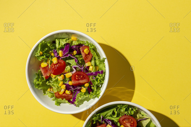 Fresh lettuce salad with Cherries tomatoes, red onion and corn, sunlight on pink background from above. Healthy food. Vegan food.