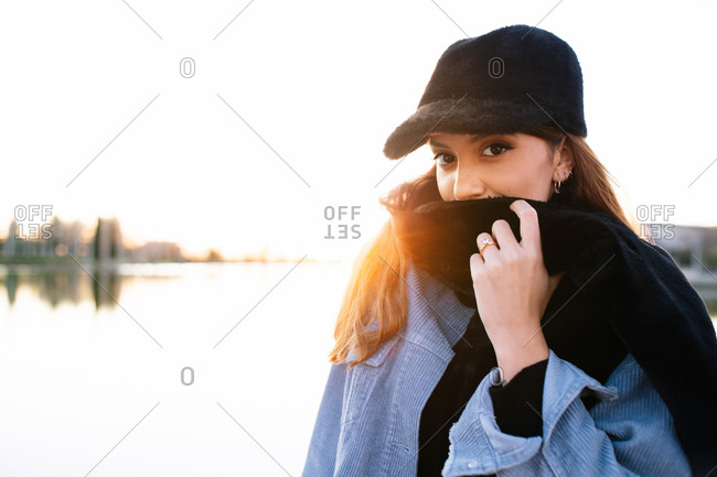 Charming woman in casual wear on shore of lake