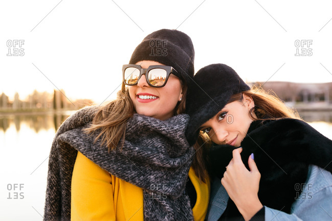 Pleased woman in warm clothing and sunglasses with stylish female friend during trip on lake at sunset