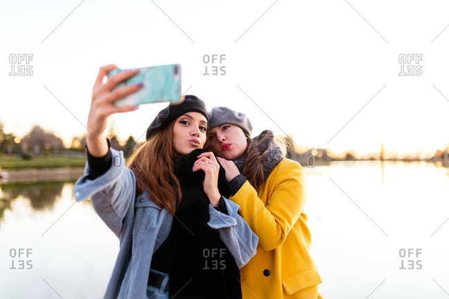 Young ladies in stylish warm wear and berets taking selfie with mobile phone standing on shore of peaceful lake in sunset on blurred background