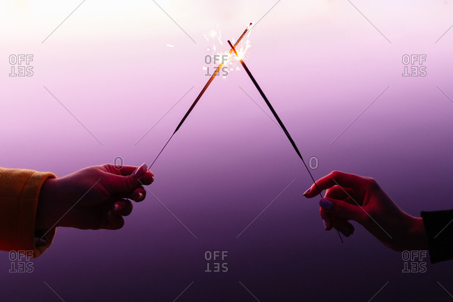 Crop female hands in front of each other holding burning sparklers on colorful purple background
