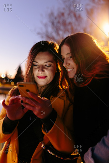 Content female friends in casual warm clothing smiling while surfing mobile phone with evening sky on blurred background